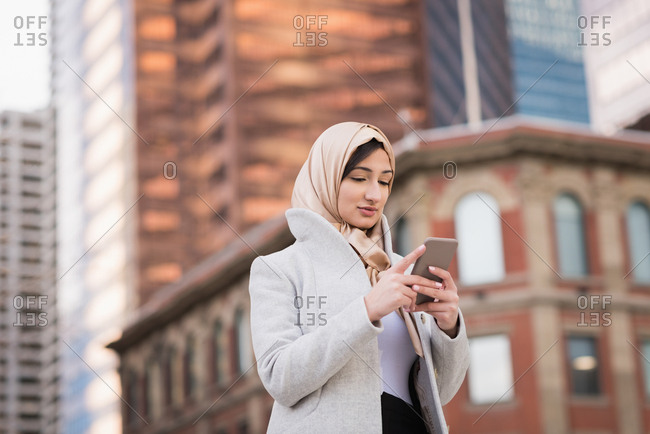 Woman in hijab using mobile phone in city