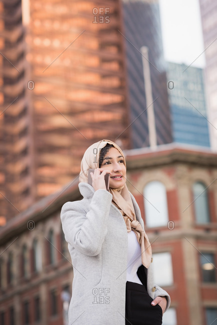 Woman in hijab talking on mobile phone in city