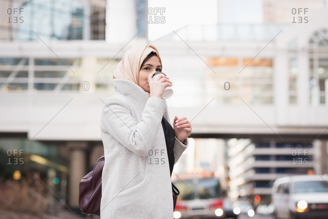 Woman in hijab drinking coffee on city street