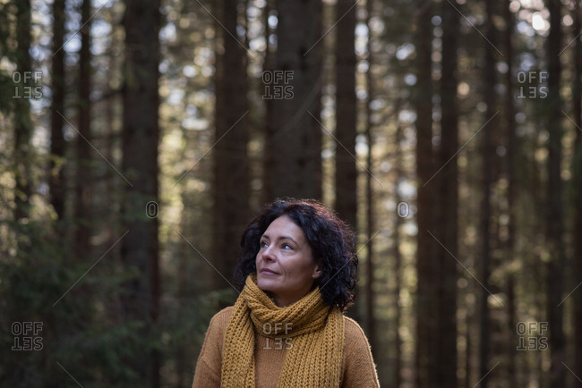 Thoughtful female hiker standing in forest