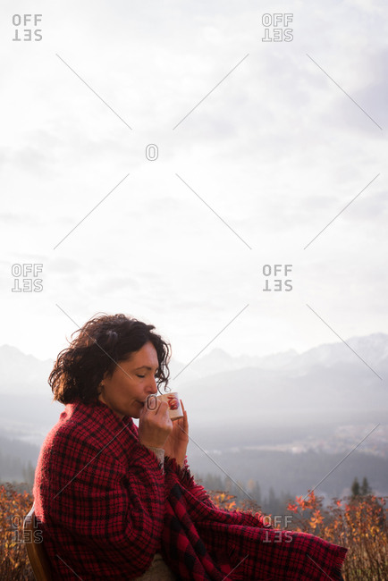 Female hiker in blanket having coffee on a sunny day