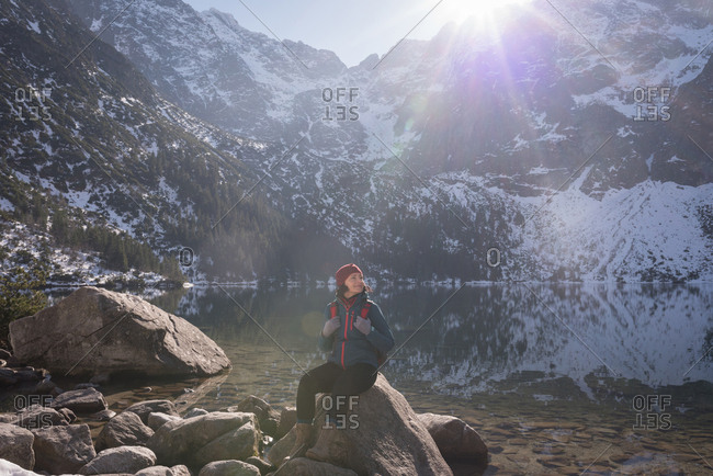 Female hiker sitting on rock at lakeside during winter