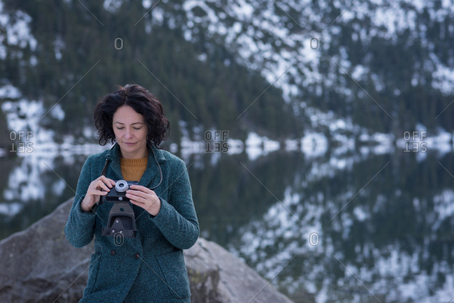 Woman reviewing picture on digital camera during winter