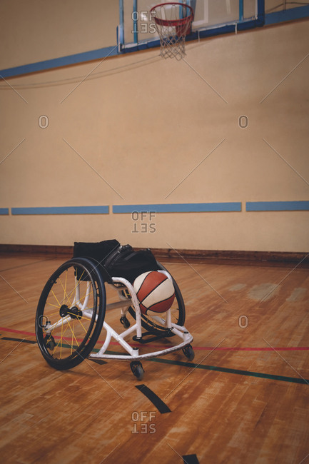 Empty wheelchair and basket ball in the court