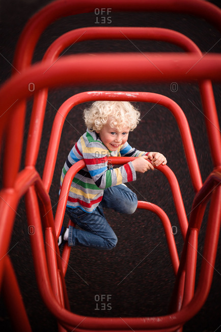 Boy climbs on playground equipment