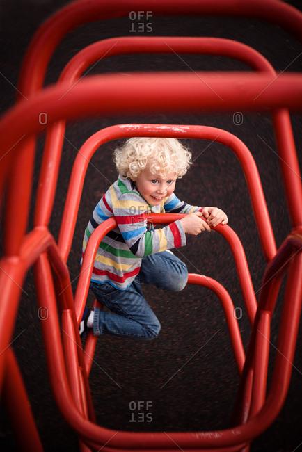Boy climbs on playground equipment