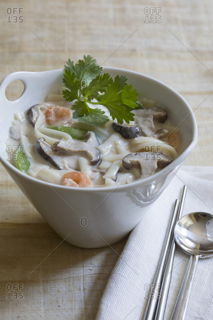 Asian mushroom, noodle, shrimp soup in white  bowl