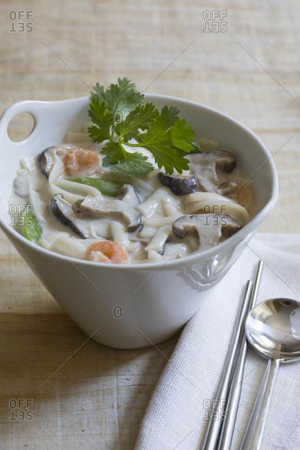 Asian mushroom, noodle, shrimp soup in white  bowl