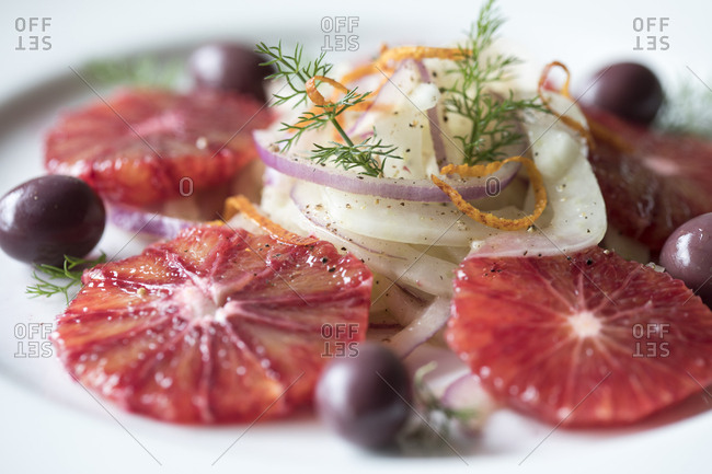 Citrus salad with blood oranges, fennel on white plate