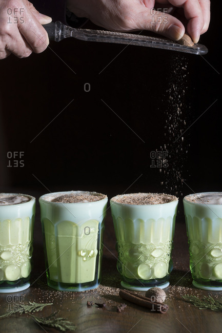Side view of 4 glasses of eggnog with nutmeg being ground on top