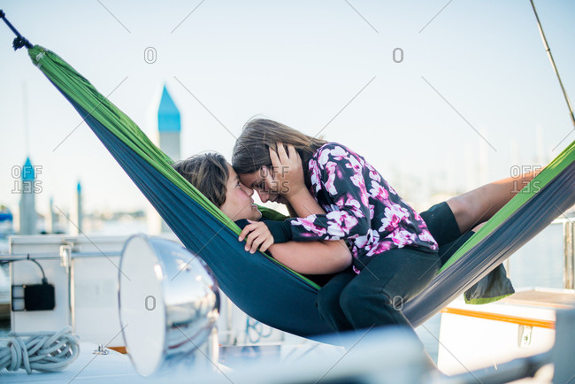 Brother and sister playing on in a hammock on a sailboat