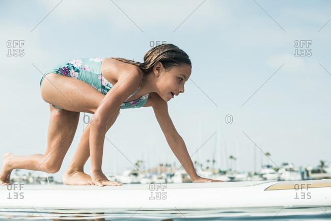 Young girl playing on a stand up paddleboard in the ocean