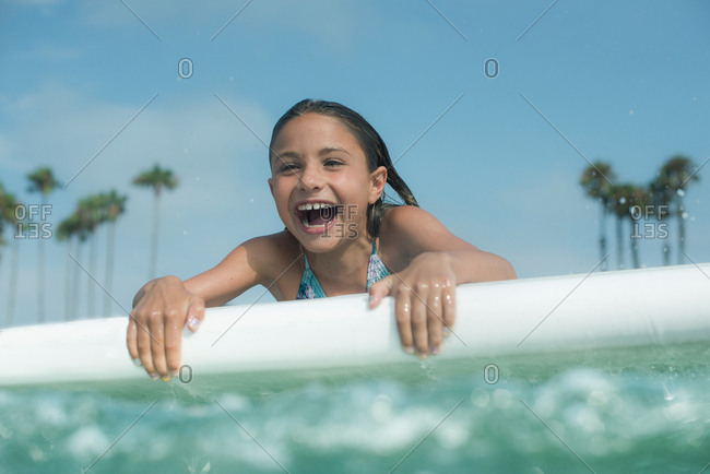 Young girl playing on a paddleboard in the ocean