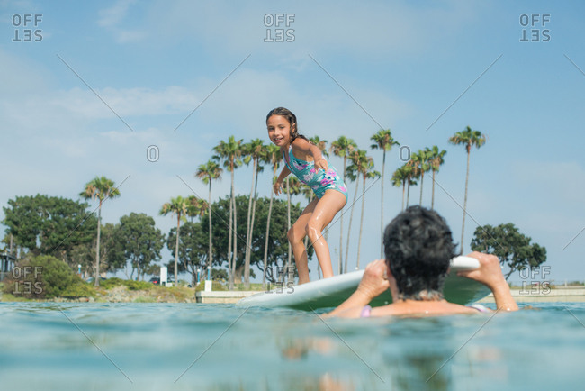 Young girl playing on a stand up paddleboard in the ocean with her grandmother