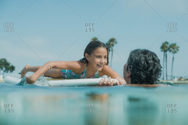 Young girl on a paddleboard in the ocean with her grandmother