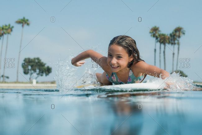 Young girl paddling on a paddleboard in the ocean