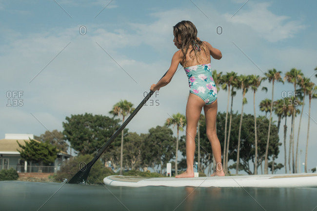 Girl on a paddleboard paddling in the ocean