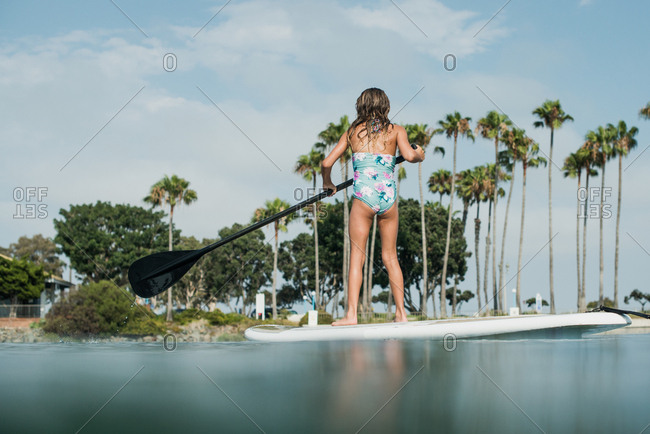 Girl on a paddleboard paddling in the ocean in California