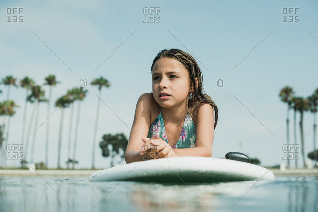 Young girl floating on a paddleboard in the ocean