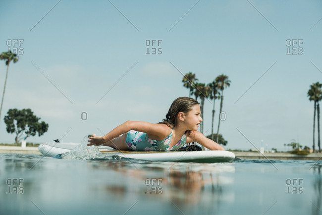 Young girl paddling on a paddleboard in the ocean in California