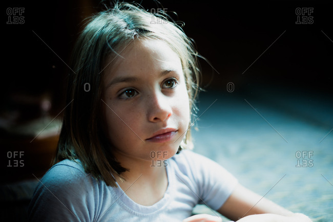 Girl inside a boat with sidelight looking thoughtful