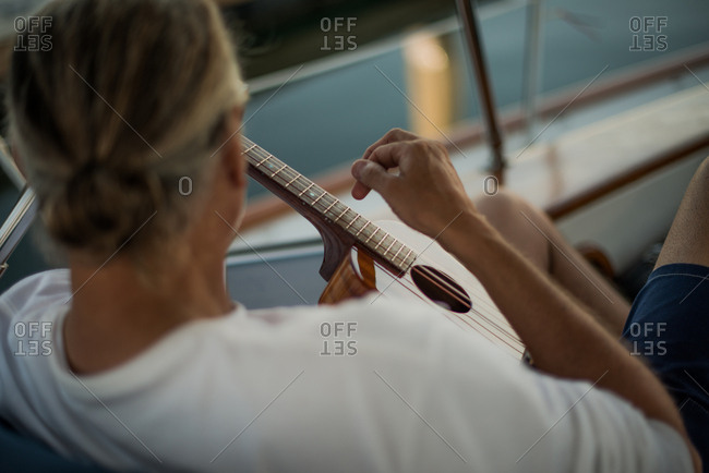 Man on a boat playing guitar