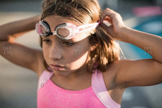 Girl putting on goggles before swimming