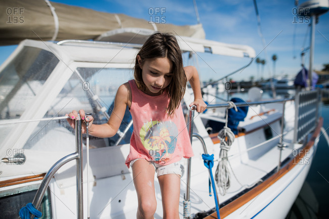Girl stepping off of a sailboat at the marina in summertime in California
