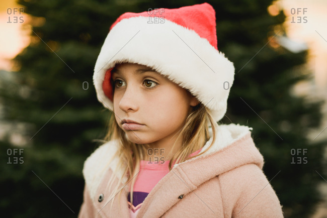 Little girl picking out a Christmas tree in a tree lot wearing a Santa hat
