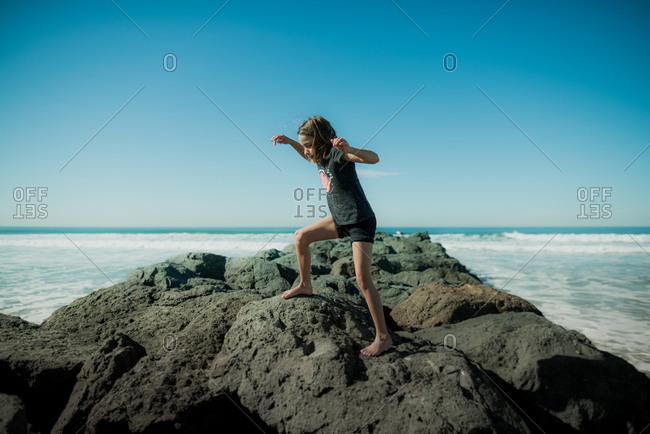 Girl climbing on the breakwater at Imperial Beach, California