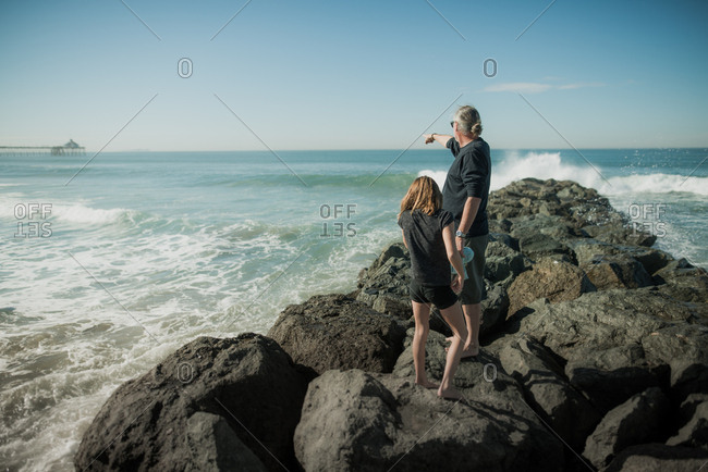 Father and daughter climbing on the breakwater at Imperial Beach, California