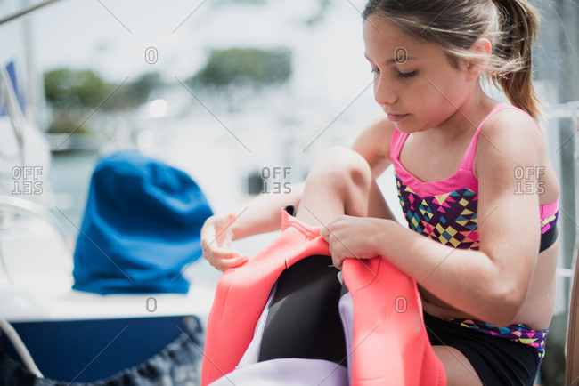 Young girl sitting on a sailboat putting on pink and purple wetsuit