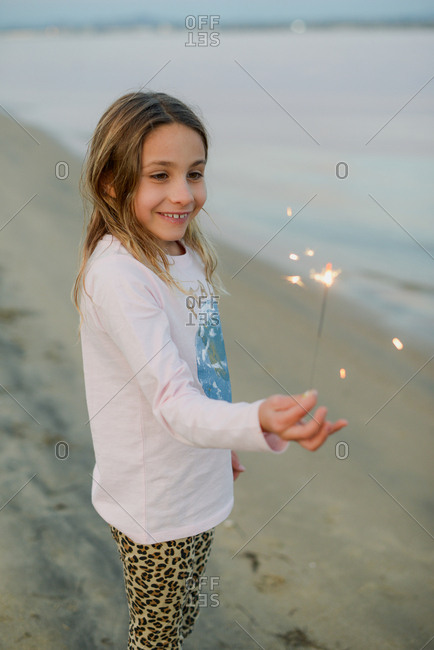 Young girl playing with sparklers on the beach in San Diego at sunset