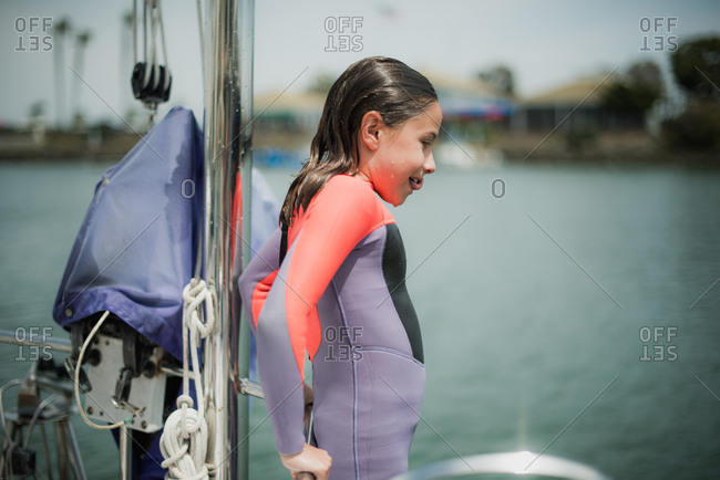 Young girl jumping from a sailboat wearing a pink and purple wetsuit