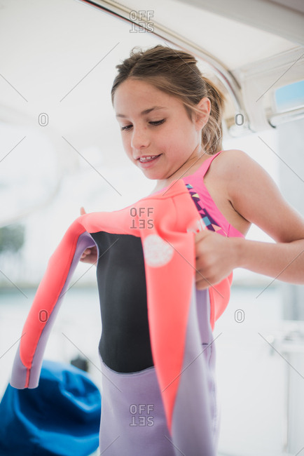 Young girl on a sailboat putting on pink and purple wetsuit
