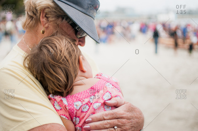 Baby girl sitting with grandmother at the beach in the summer