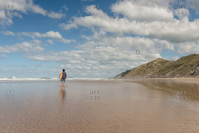 Boy carrying surfboard on the coast of New Zealand