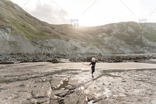 Boy running with stick on a beach in New Zealand
