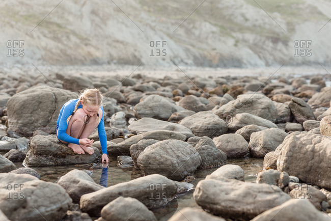 Girl looking into water on the rocky coast of New Zealand