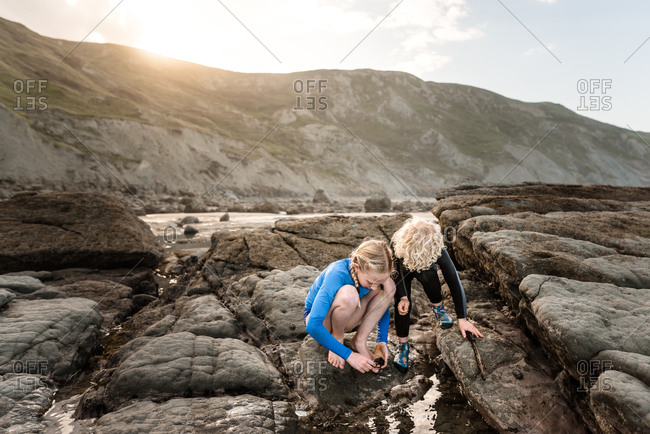 Two kids looking into water on the rocky coast of New Zealand