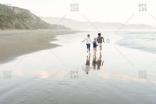 Three kids running on the coast of Hawke's Bay, New Zealand