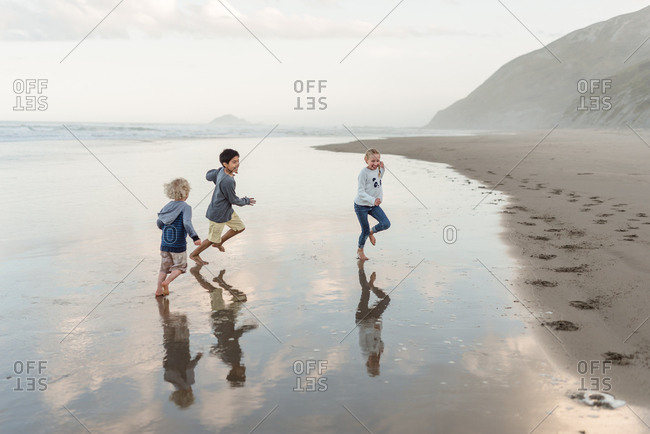 Three kids running in water on the coast of Hawke's Bay, New Zealand