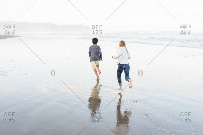 Two kids running in water on the coast of Hawke's Bay, New Zealand