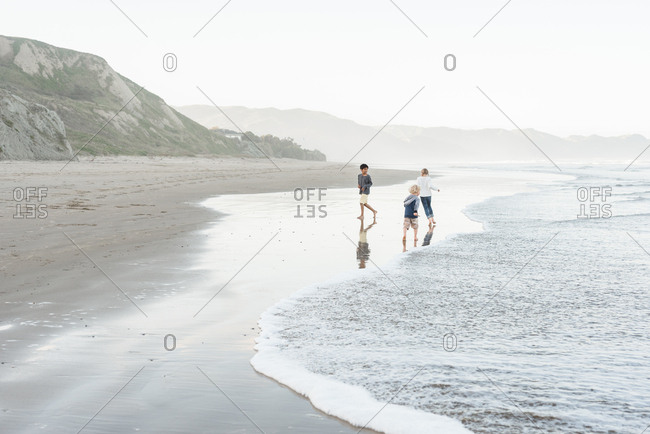 Kids running in water on the coast of Hawke's Bay, New Zealand