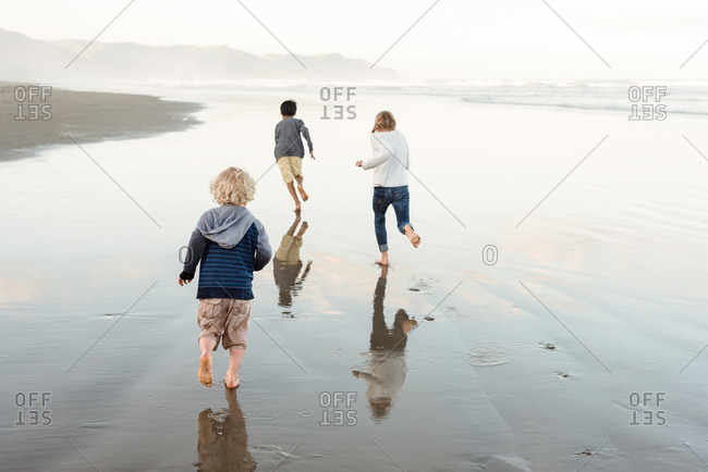 Three siblings running on the coast of Hawke's Bay, New Zealand