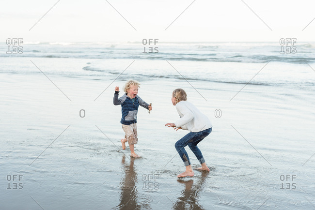 Two siblings playing on the coast of Hawke's Bay, New Zealand