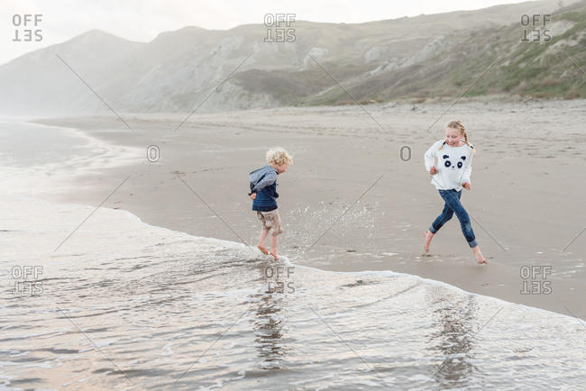 Young kids playing on the coast of Hawke's Bay, New Zealand