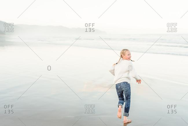 Blonde girl running on beach in New Zealand