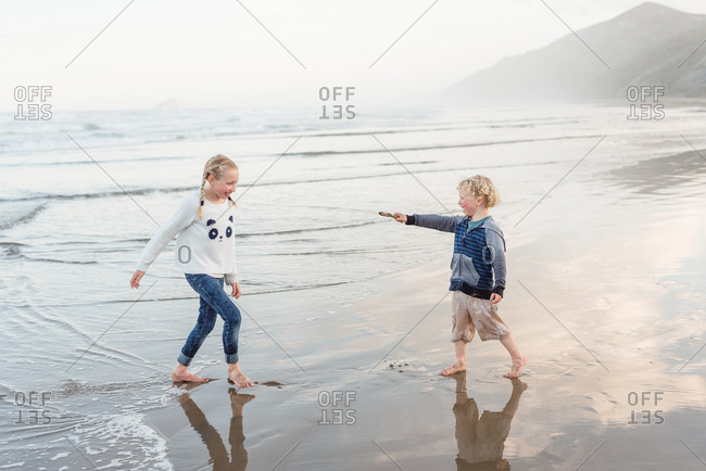Two kids playing on the coast of Hawke's Bay, New Zealand