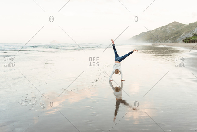 Blonde girl doing cartwheel on beach in New Zealand